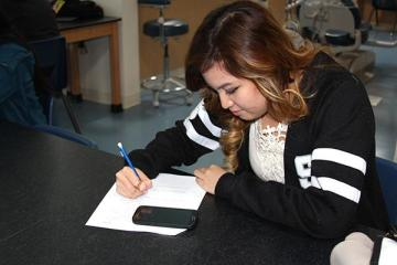 """Senior Lichelle Gaerlan writes a thank you letter to Mr. Pate Thomas after he nominated her for the Silver State Credit Union's Teen of the Month. Gaerlan won a $100 gift card for her academic excellence and community service work. """"I plan on taking Thomas out for lunch with a portion of the money, and I want to save the rest for college,"""" Gaerlan said. Photo Credit: Helen Abraha"""