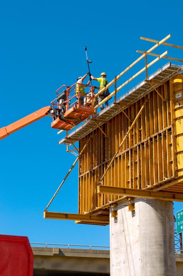 Carpenters assist a Surveyor while building a safety rail around the top of a concrete form.