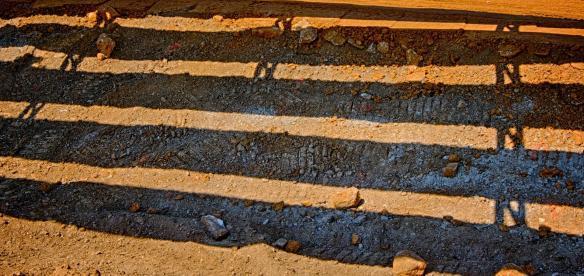 "Shadow pattern of cross bracing and steel girders making an ""N"" on the earth."