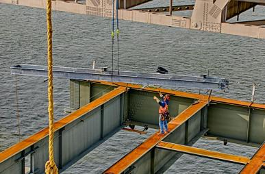 Charlie Draper guides catwalk section into place for the downtown span of the Ohio River Bridges Project in Louisville, Kentucky.