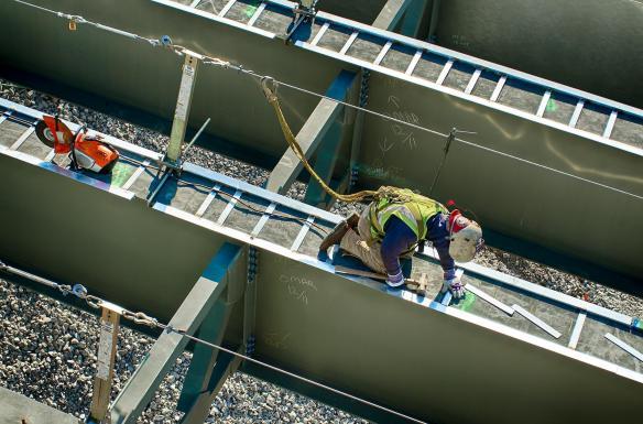 Ironworker welding on a bridge girder.