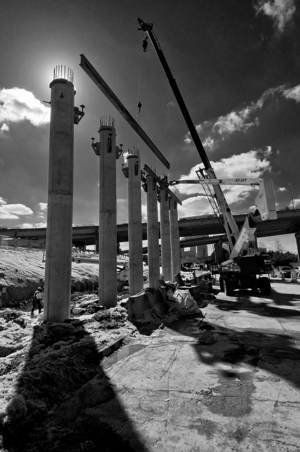 "Carpenters placing a support beam for the ""dance floor"" which will support the concrete forms for another bridge support beam.#3 - Topaz B&W Version"
