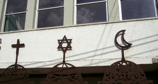 Jewish Star of David, Arab- Christian Cross and Crescent on the front of Beit Hagefen, Arab-Jewish Center in Haifa since 1963./Flickr photo by zeevveez