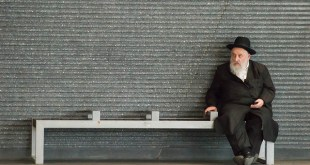 An orthodox Jew casually checks his mobile phone while sitting on a bench in Antwerp Central Station./Flickr photo by Jaap Joris