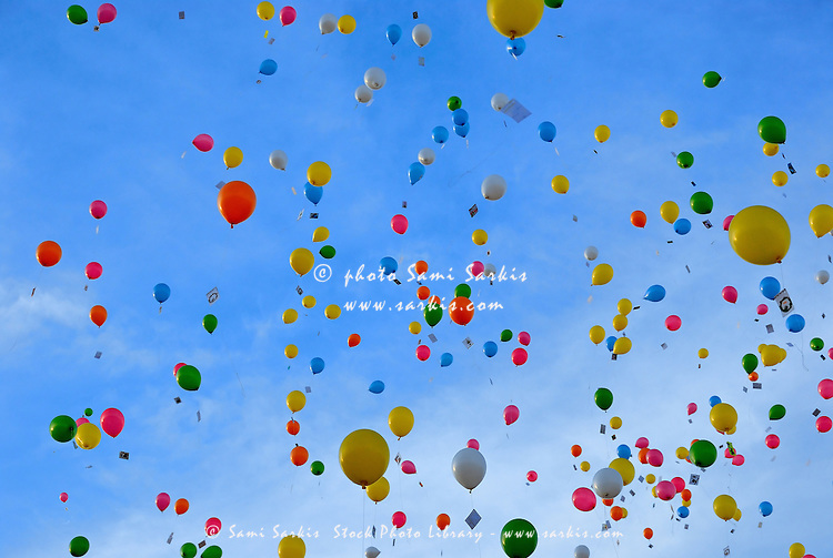 Brightly colored balloons floating across a blue sky Sami Sarkis