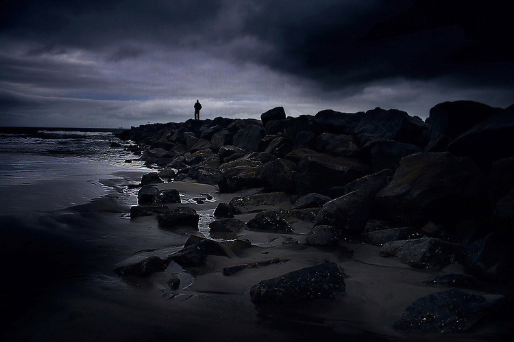 Shine Quote Wallpaper Distant Male Figure On Rocky Beach Trigger Image