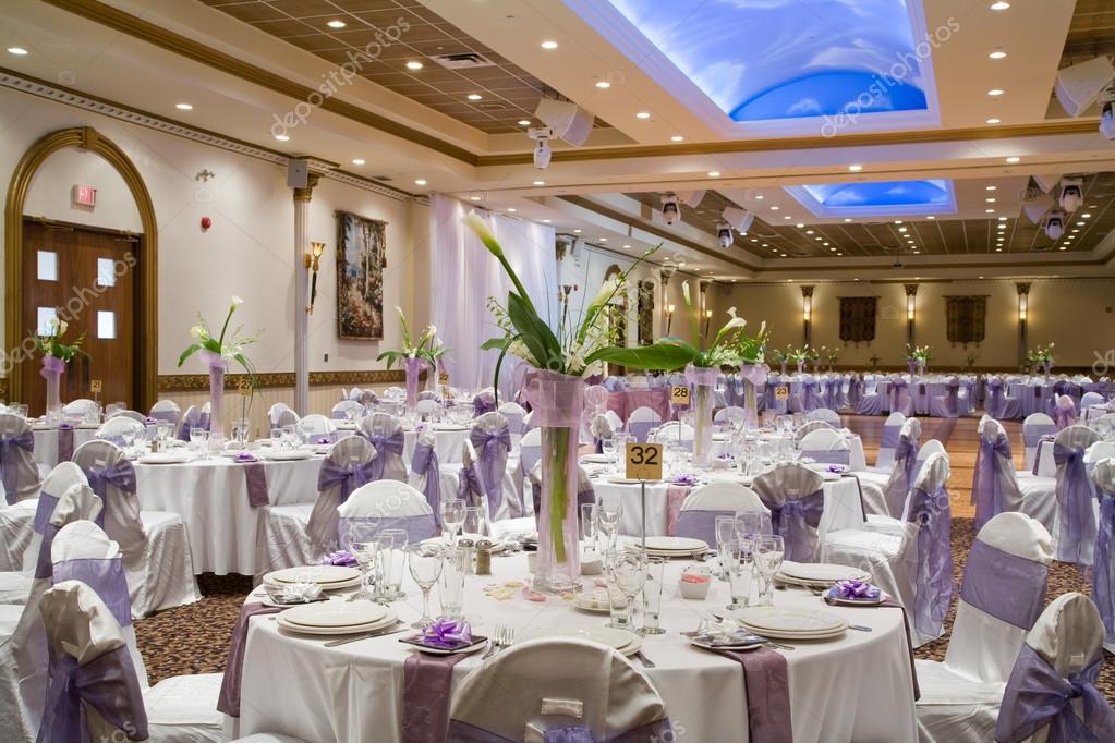 Indoor wedding reception hall with round tables and floral cent - wedding reception round tables