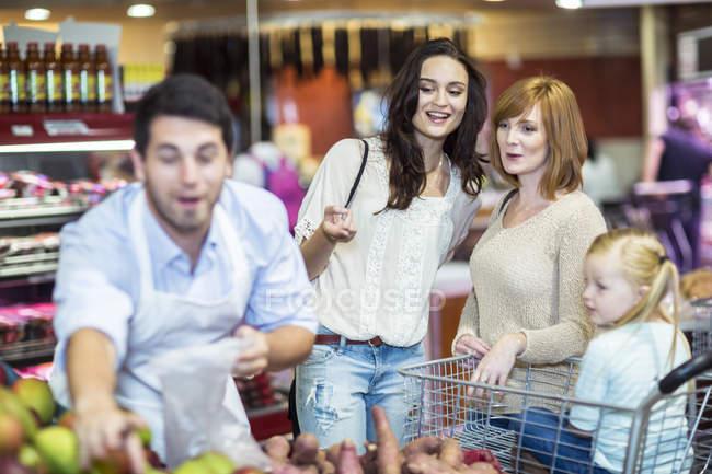 Shop assistant helping customers choosing fruits \u2014 Stock Photo - shop assistan