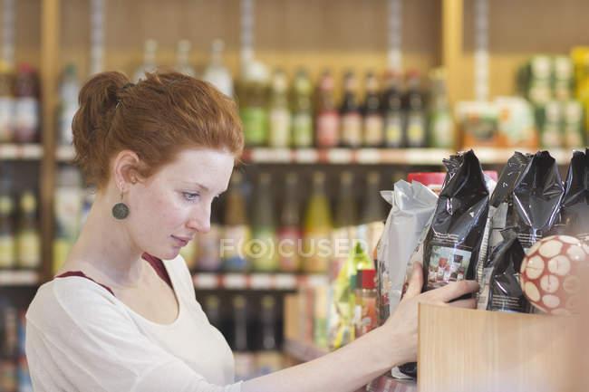 Female shop assistant sorting merchandise in wholefood shop \u2014 color