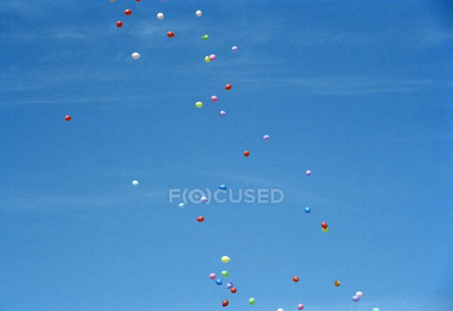 Colored balloons floating in clear sky \u2014 Stock Photo #180090238
