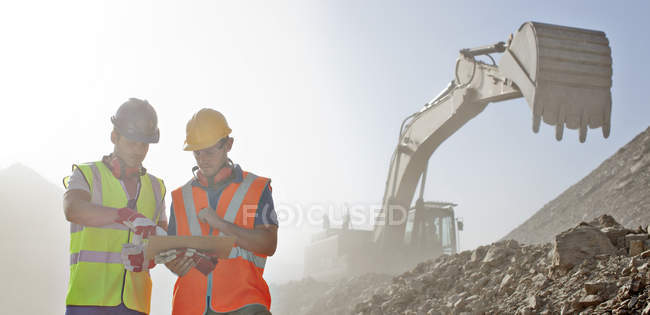 Workers reading blueprints in quarry \u2014 background, commercial
