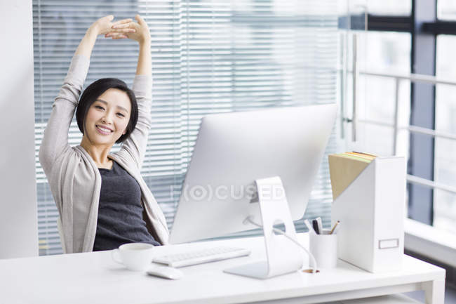 Chinese woman stretching and relaxing in office \u2014 professional