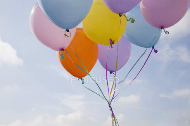 Bunch of colorful balloons floating in air against blue sky \u2014 copy