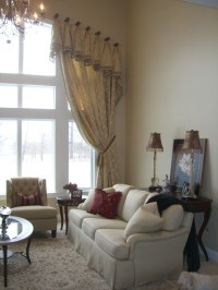 Formal great room with arched window treatment ...