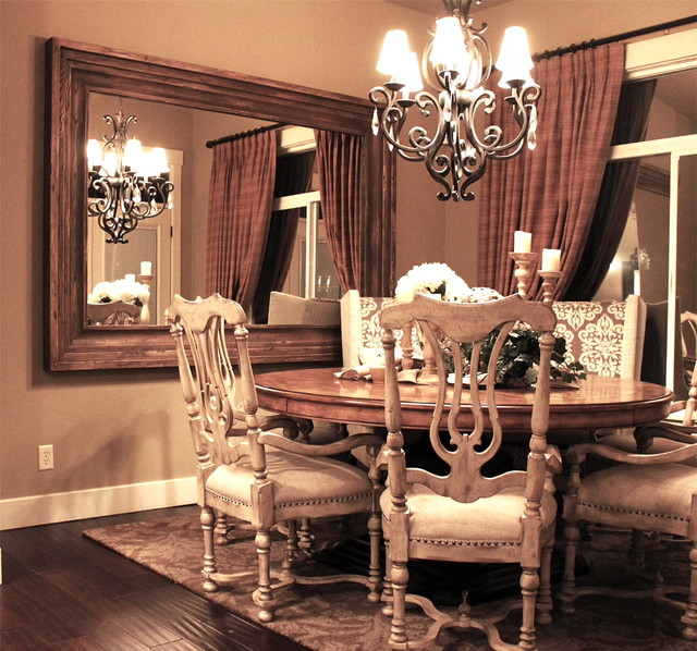 Large wood-framed mirror mounted on the dining room wall Dining