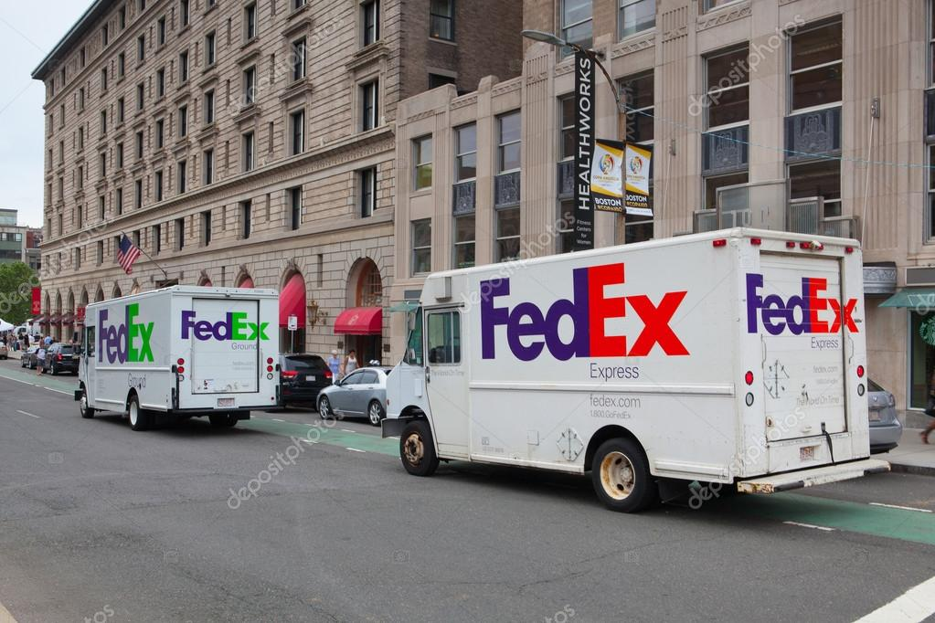 FedEx Ground truck and FedEx Express truck on the same street in