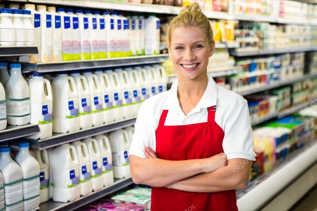 Smiling shop assistant with arms crossed \u2014 Stock Photo - shop assistan