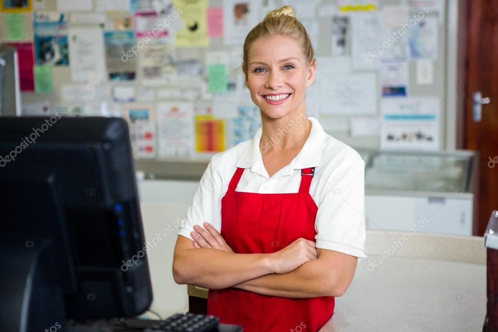 Smiling shop assistant with arms crossed \u2014 Stock Photo