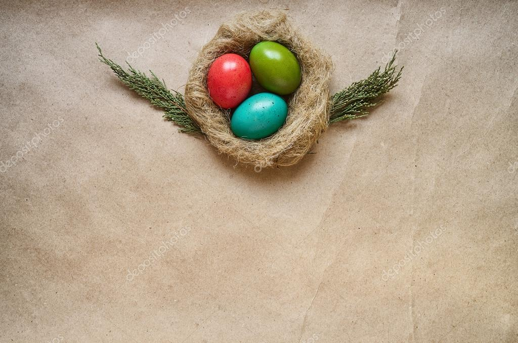 Nest with colored eggs on eco craft paper background Easter