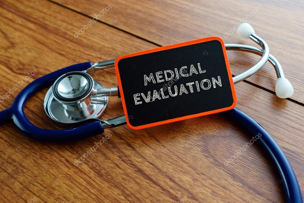 Word MEDICAL EVALUATION with stethoscope on wooden table \u2014 Stock