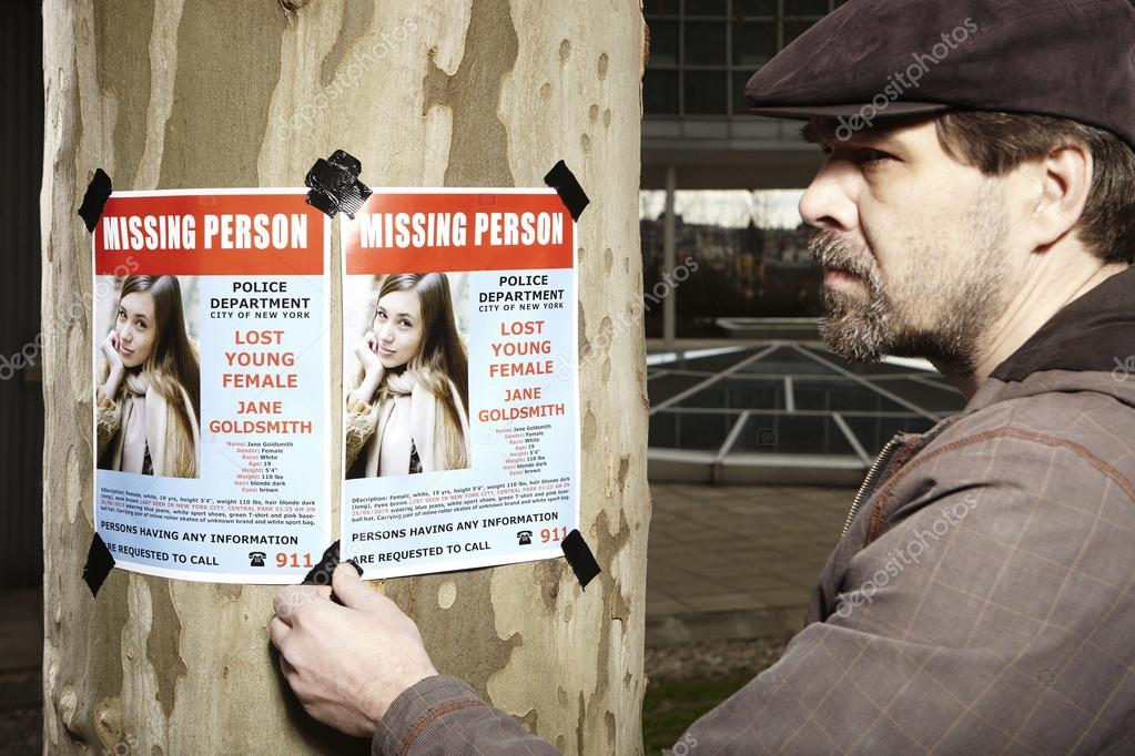 Police man taping missing person poster to tree in park \u2014 Stock