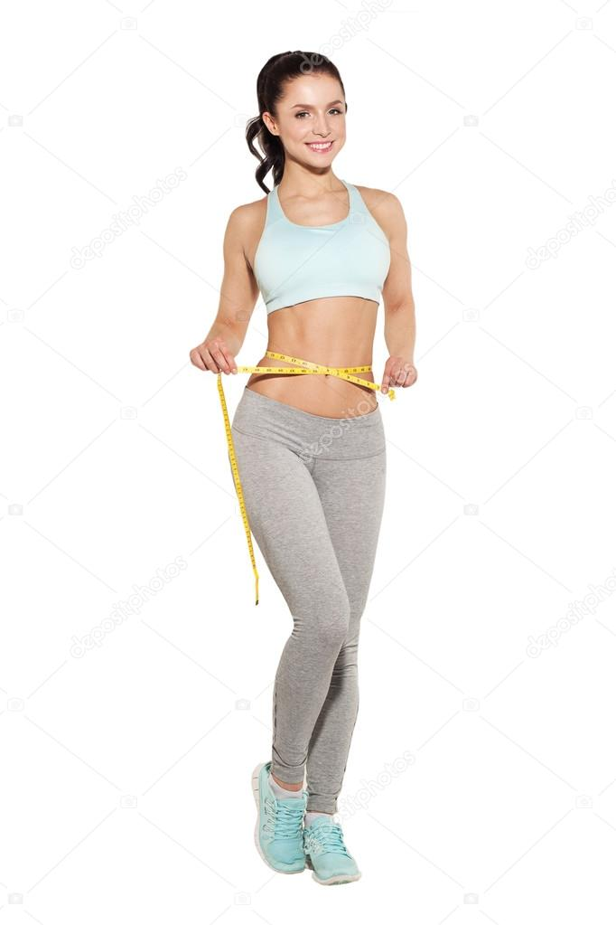 Weight loss, sports girl measuring her waist, training in the gym