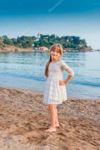 Cute little girl standing on sand beach, wearing white ...