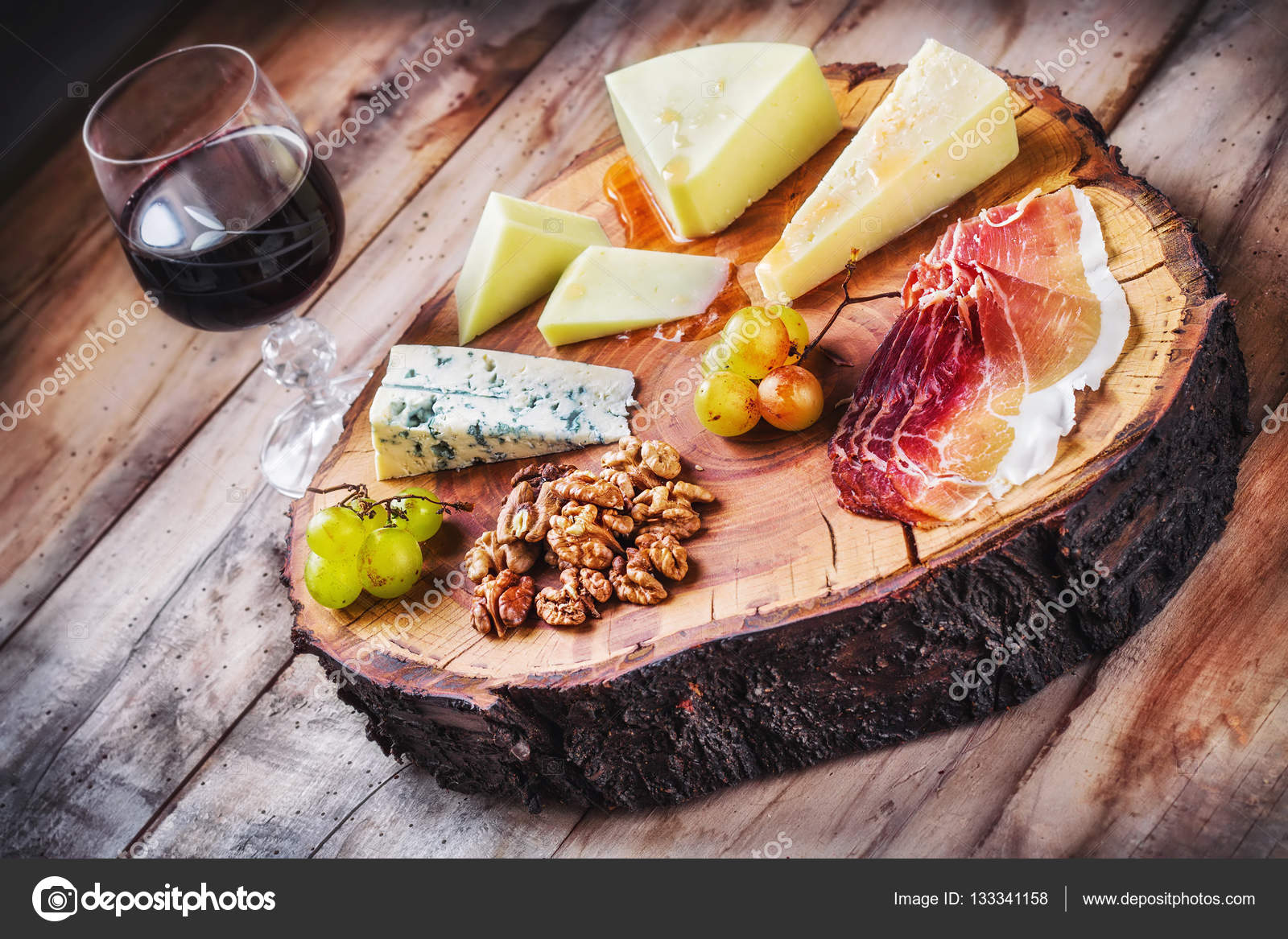 Mediterrane Küche An Bord Rustic Mediterranean Cheese Board And A Glass Of Red Wine Stock
