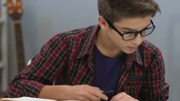 Smart teenager in glasses checking information in books, writing