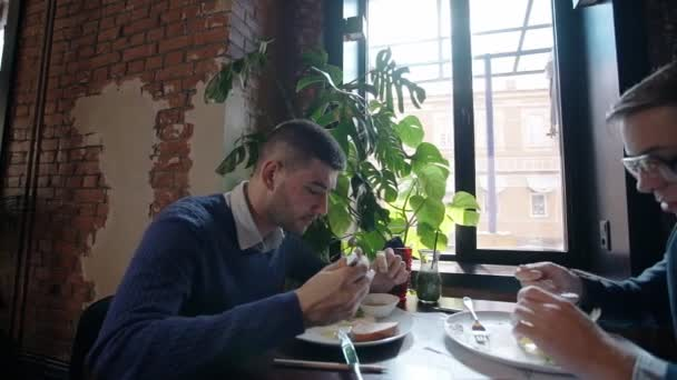 Two businessmen having breakfast together in the cafe after