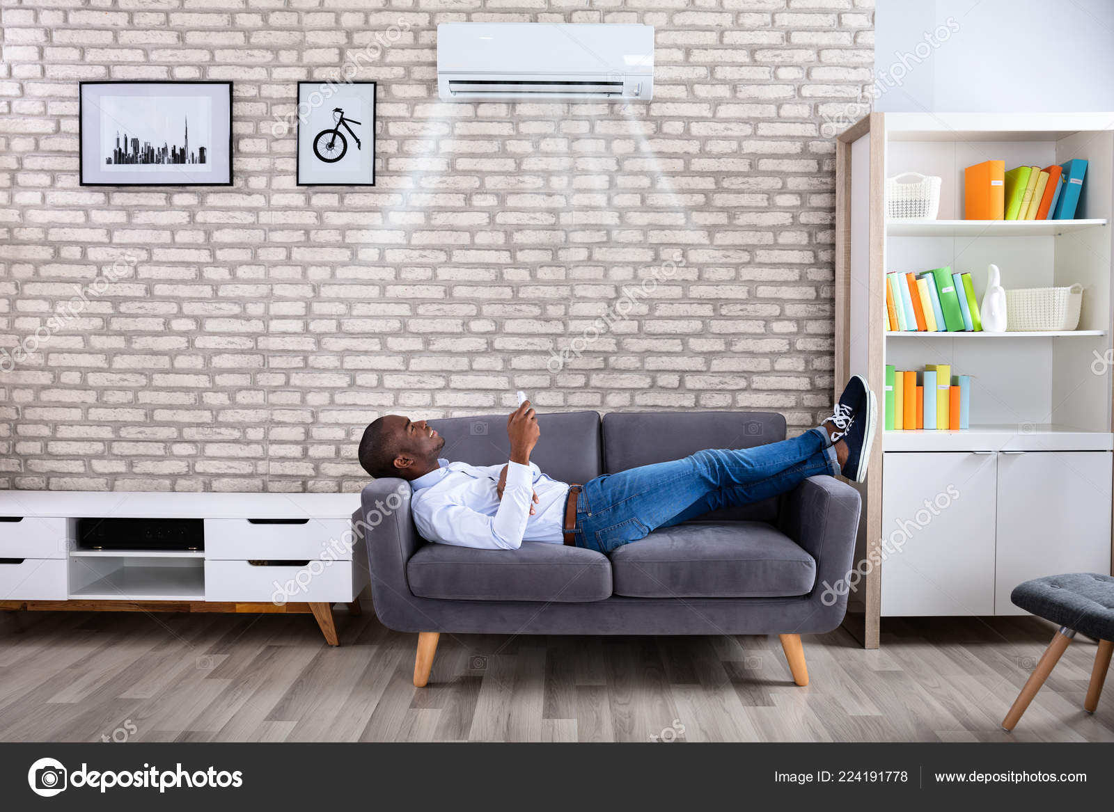 Air Sofa ár Young African Man Relaxing Sofa Operating Air Conditioner Remote