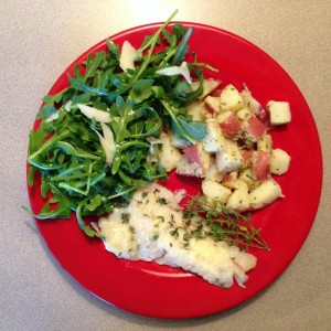 Baked fish and French potato salad with arugula salad