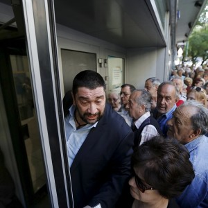 A bank manager tries to keep order as pensioners line up outside a National Bank in Athens, Greece on Wednesday. Yannis Behrakis | Reuters