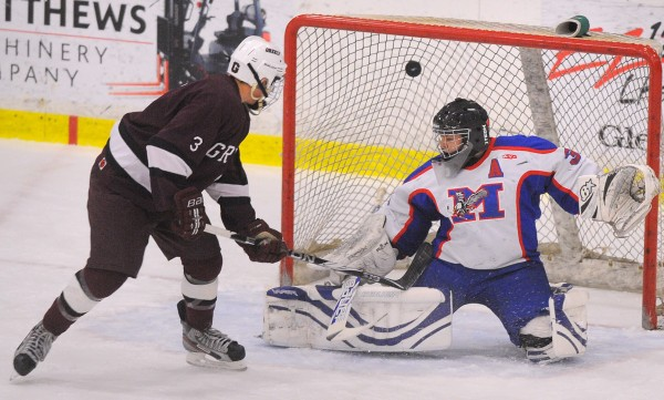 Greely High School's Ben Hackett (left) puts the puck in the net past Messalonskee High School's goalie Nathan DelGiudice. Hackett scored the team's second goal during the first period of the State Class B Championship game. Greely won the game 6-2.