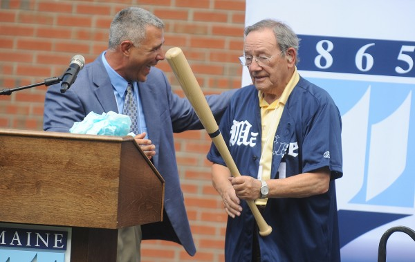 After presenting him with a team jersey, UMaine baseball head coach Steve Trimper presents UMaine trustee Paul Mitchell (right) with an honorary bat embossed with Mitchell's name during Tuesday's dedication ceremony for the new Paul Mitchell Batting Pavilion at the University of Maine in Orono. Coach Trimper was laughing because Mitchell had j