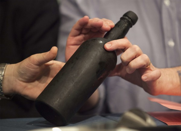 Sommeliers Larry Stone and Paul Roberts, both of Napa, California, inspect a bottle recovered from a shipwreck at the Wine + Food Festival in Charleston, South Carolina, March 6, 2015. A bottle of wine recovered intact four years ago from the 1864 wreck of a Civil War blockade runner that sank off the coast of Bermuda was uncorked and sipped by a panel of experts on Friday during the food festival in Charleston, South Carolina.