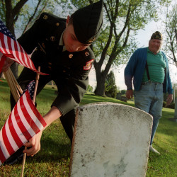 Nate Hicks (left) of the Bangor High School ROTC distributes flags Wednesday afternoon on the gravestones of veterans around Mount Pleasant Cemetery in Bangor. Raymond Willins (right), a World War II veteran and a member of American Legion Post 12 in Bangor, was the leader of Hicks' group. American Legion Post 12, the Bangor High School ROTC, Bangor Boy Scout Troops 301 and 10, and community volunteers gathered at the cemetery for a brief ceremony and the placement of flags for Memorial Day.