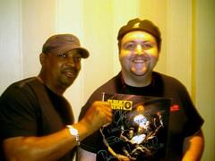 Hip Hop emcee legend Chuck D of Public Enemy poses with DJ B-Naut and a freshly autographed Public Enemy album.