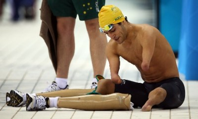 Ahmed Kelly of Australia re-attaches his prosthetic legs after competing in the men's 50m ...