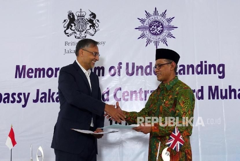 Ketua Umum Pimpinan Pusat Muhammadiyah Haedar Nasir (kanan) dan Duta Besar Inggris untuk Indonesia Moazzam Malik bertukar nota kesepahaman bersamai usai ditandatangani bersama, Senin (16/5) di Jakarta.  (Republika / Darmawan)