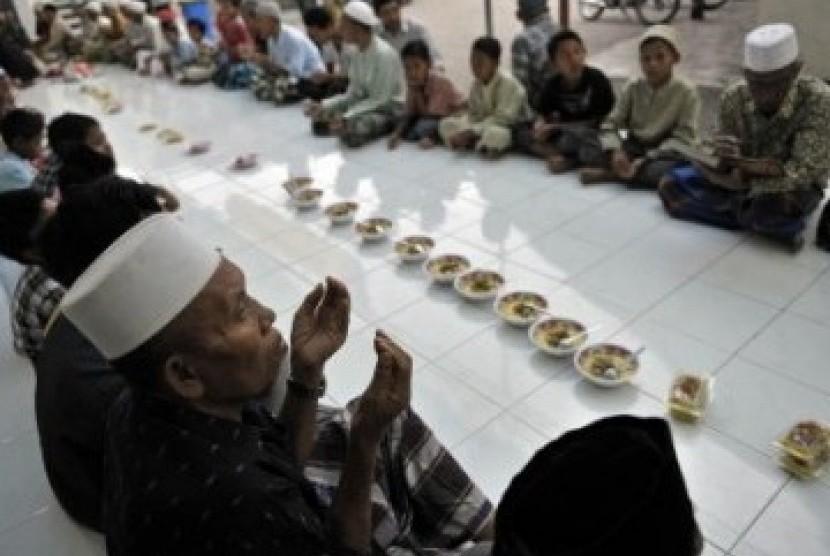 Umat Islam berdoa sebelum menggelar tradisi 'Megibung' di Masjid Al Muhajirin Kampung Islam Kepaon, Denpasar, Bali, Rabu (10/8).