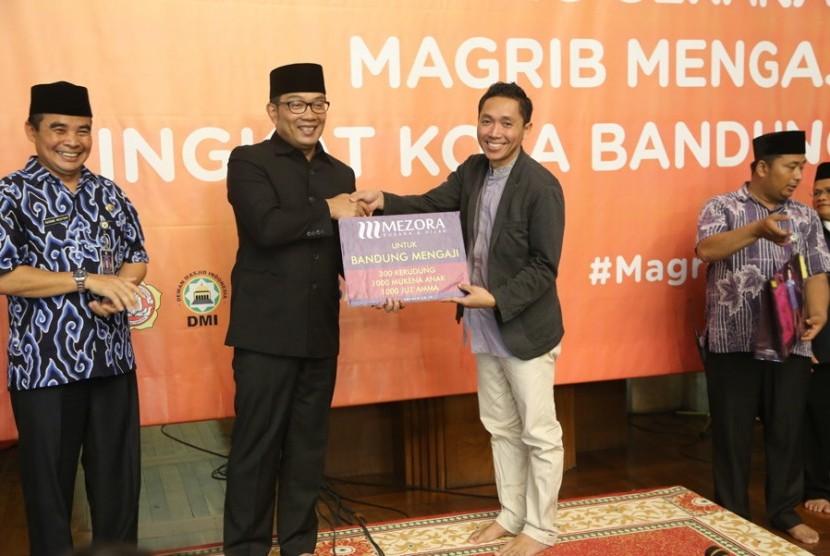 Wali Kota Bandung, Ridwan Kamil, menerima bantuan juzz amma dan mukena yang menjadi program Maghrib Mengaji