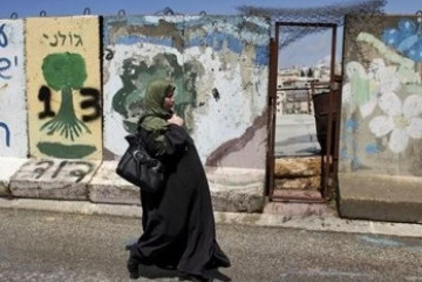 Wanita Palestina tengah berjalan di depan tembok beton yang memblokade kota Hebron, Tepi Barat.
