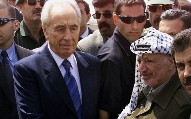 Palestinian leader Yasser Arafat (right), shakes hands with Israeli then-foreign minister Shimon Peres (left) after their meeting at Gaza International Airport, southern Gaza Strip, September 26, 2001. (AP/Laurent Rebours, File)