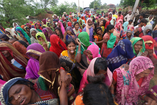 Relatives of victims grieving after 10 people were killed in a land dispute in the Indian state of Uttar Pradesh on Wednesday.