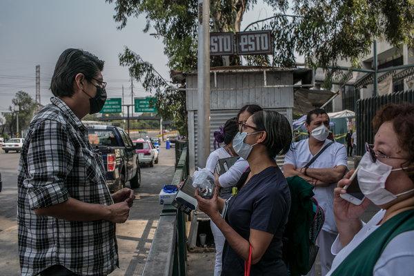 Ivette Díaz, centro, enfermera de cuidados intensivos en el hospital La Raza, que compra gafas de seguridad y guantes de látex a un vendedor ambulante.