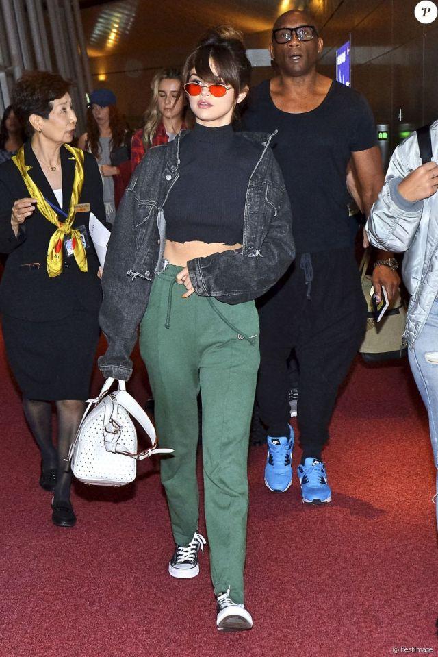 Selena Gomez à l'aéroport de Narita à Tokyo, habillée d'une veste Sami Miro Vintage, d'un crop top, d'un jogging Vetements (collection printemps-été 2016) et de baskets Converse. Un sac Louis Vuitton (modèle SC) et des lunettes de soleil complètent sa tenue. Le 1er août 2016.