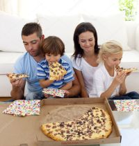 Family eating pizza in living