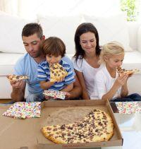 Family eating pizza in living