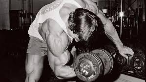 Arnold Schwarzenegger doing dumbbell bicep curls